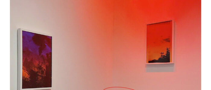 Image of Lionel Cruets photographs hanging on two walls with a red lights on the right most photograph